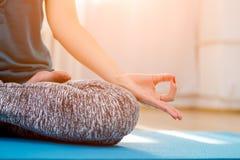 Woman sitting in lotus yoga pose in studio Stock Photos
