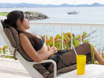 Woman sitting in lounge chair by the beach Royalty Free Stock Photography