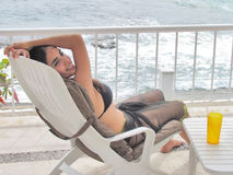 Woman sitting in a lounge chair by the beach Royalty Free Stock Photos
