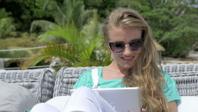 Woman sitting in lounger using digital tablet during vacation. Young blonde woman reading e-book in tropical resort. Woman relaxing with tablet computer while stock footage