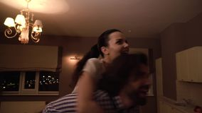 Woman is sitting on man`s back. They are entering room together. Girl is looking to left and right. She is excited and. Amazed. Guy turns them around couple stock video