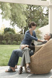 Woman Sitting On Man's Lap In Lawn. Full length of women sitting on man's lap in lawn Royalty Free Stock Photos
