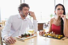 Woman sitting while man talking on mobile phone Royalty Free Stock Photos