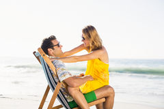 Woman sitting on mans lap at beach Stock Photos