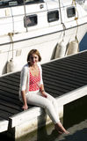 Woman sitting on marina jetty Stock Images