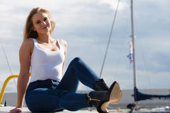 Woman sitting on marina Stock Photography