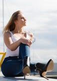 Woman sitting on marina Stock Image