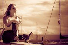 Woman sitting on marina Royalty Free Stock Images