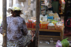 Woman sitting on a market stall from behind. A woman in a black and white leopard dress and a white hat sitting on a market stall in Asia Royalty Free Stock Photo