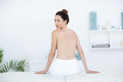 Woman sitting on massage table. In medical office Stock Photography