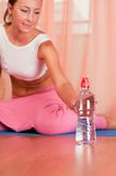 Woman sitting on mat and holding bottle of water Stock Photography