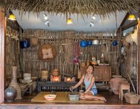 Woman sitting on mat in traditional Thai kitchen royalty free stock image