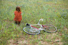 Woman sitting in meadow with bicycle Stock Photos