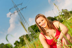 Woman sitting in meadow or field Stock Photo
