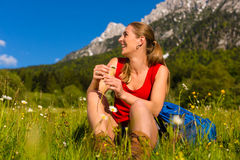 Woman sitting in meadow with mountain view Royalty Free Stock Image
