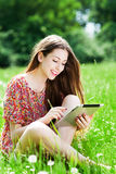 Woman sitting in meadow using digital tablet Stock Photography