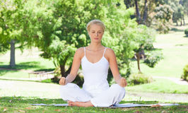Woman sitting on the meadow in yoga position Royalty Free Stock Photos