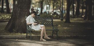 Woman Sitting on Metal Bench on Park While Reading Book Royalty Free Stock Photography