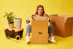 Woman sitting in the middle of moving boxes. People moving new place and repair concept. Yellow background royalty free stock photo