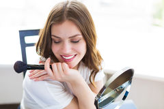 Woman sitting by the mirror. And applying makeup Stock Images