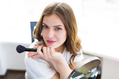 Woman sitting by the mirror. And applying makeup Stock Photos