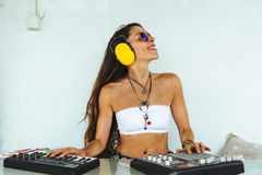 Woman sitting with mixing table, producing music while dancing. Woman sitting at the mixing table and computer, producing electronic music on a sunny day in Royalty Free Stock Photo
