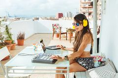 Woman sitting with mixing table, producing music on a sunny day. Woman sitting at the mixing table and computer, producing electronic music on a sunny day in Stock Photo