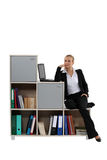 Woman sitting by modern bookcase Royalty Free Stock Images
