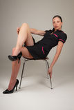 Woman sitting on modern chair. Wearing retro waitress uniform and high heels Royalty Free Stock Photography