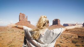 Woman sitting in Monument Valley with red rocks overview, raising her arms. stock video