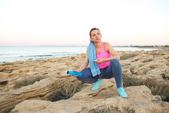 Woman sitting after morning running on the rocks by the sea Royalty Free Stock Images