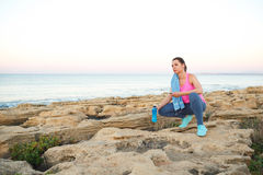 Woman sitting after morning running on the rocks by the sea Royalty Free Stock Photo