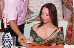Woman sitting in Moroccan restaurant, reading the menu and waite Stock Photos
