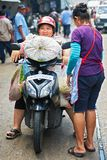 Woman sitting on a motorbike with lots of load in Bangkok royalty free stock photo