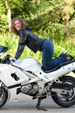 Woman sitting on a motorcycle. Beautiful young female biker sitting on a sports motorcycle Royalty Free Stock Photography