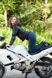 Woman sitting on a motorcycle. Beautiful young female biker sitting on a sports motorcycle Stock Photo