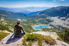 Woman sitting mountain edge above lake. Royalty Free Stock Image