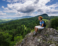 Woman sitting on a mountain peak Royalty Free Stock Photo