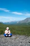 Woman sitting on mountain top. Caucasian woman sitting on mountain top and looking at camera Stock Photo