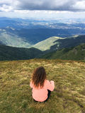 Woman sitting on mountain top. A woman sitting on the mountain top enjoying the view Royalty Free Stock Photography