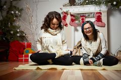 Woman sitting near the Christmas tree with her daughter Stock Photography