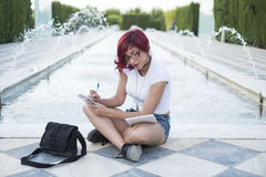 Woman sitting near a fountain notes with a notebook Royalty Free Stock Photos