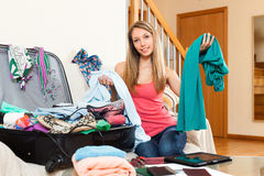 Woman  sitting near opened overfull suitcase. Smiling woman with clothes in hands sitting near opened overfull suitcase Stock Photos