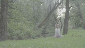 Woman sitting near the river with singing bowl. Attractive woman sitting near the river in a park with singing bowl in her hands. Then she starting to do yoga stock footage