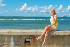 Woman sitting near the sea. Royalty Free Stock Image