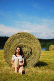 Woman sitting near the straw bale Royalty Free Stock Photo