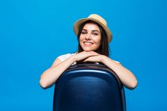 Young Woman sitting near a suitcase baggage on a blue background. Woman sitting near a suitcase on a blue background Stock Photography