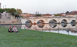 Woman sitting near the Tiberian bridge over the channel Stock Images