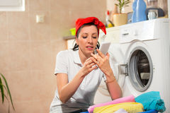 Woman sitting near the washing machine and using phone Royalty Free Stock Photo
