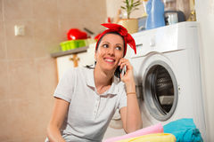 Woman sitting near the washing machine and using phone Royalty Free Stock Photos